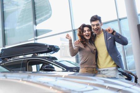 glücklicher Mann mit Brille umarmt lockige attraktive Frau, während er Triumph im Autohaus feiert