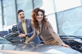 selective focus of happy curly woman smiling near excited man in glasses in car showroom