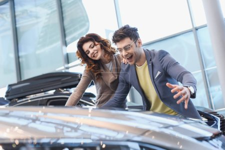 selective focus of happy man and girl smiling while looking at car