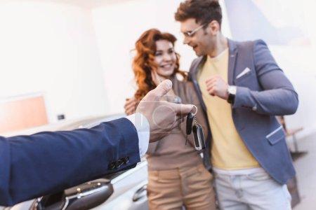 Photo pour Foyer sélectif du concessionnaire de voiture tenant les clés près de l'homme et de la femme gais dans la salle d'exposition de voiture - image libre de droit