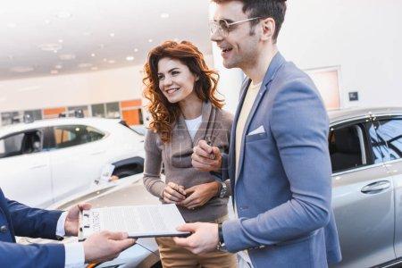Photo pour Recadrée vue de concessionnaire de voiture tenant le presse-papiers avec contrat près de l'homme heureux dans les lunettes et la femme bouclée - image libre de droit