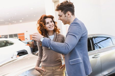 Foto de Hombre feliz en gafas mirando a la alegre mujer rizado de pie con las manos en los bolsillos en el showroom de automóviles - Imagen libre de derechos