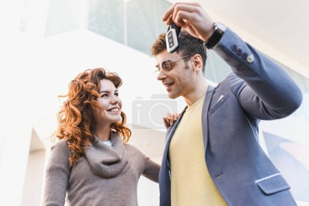Photo pour Vue de fond de l'homme gai dans des lunettes regardant la fille tout en tenant les clefs dans le showroom de voiture - image libre de droit