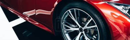 Photo for Panoramic shot of new shiny red automobile with metallic wheel - Royalty Free Image