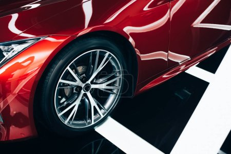Photo for Shiny new red automobile with metallic wheel in car showroom - Royalty Free Image