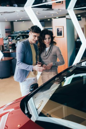 Photo for Attractive woman standing with handsome man pointing with finger at red automobile - Royalty Free Image