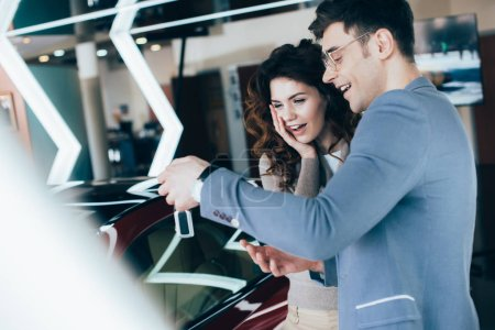 Photo for Attractive surprised woman standing with handsome man and looking at keys near car - Royalty Free Image