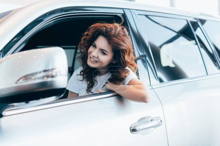 Photo for Selective focus of cheerful curly woman sitting and smiling in automobile - Royalty Free Image