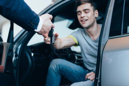 Photo pour Vue recadrée de concessionnaire de voiture donnant des clés à l'homme réussi assis dans la voiture - image libre de droit