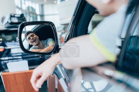 Photo for Selective focus of successful happy man smiling while looking at mirror in automobile - Royalty Free Image