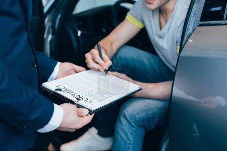 Photo pour Recadrée vue de concessionnaire de voiture tenant le presse-papiers tout succès contrat de signature homme - image libre de droit