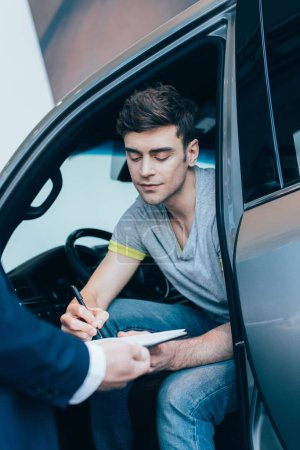 Photo for Cropped view of car dealer holding clipboard while handsome man signing contract - Royalty Free Image