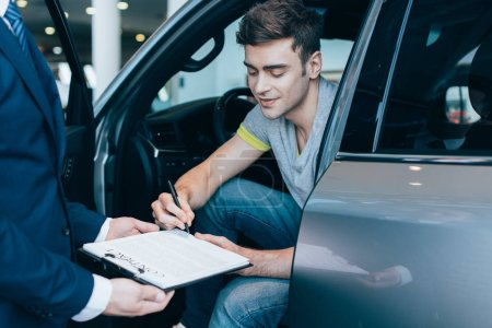 Photo pour Recadrée vue de concessionnaire de voiture tenant le presse-papiers tandis que l'homme gai signant contrat - image libre de droit