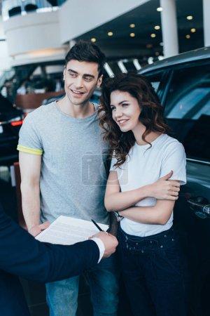 Photo pour Recadrée vue de concessionnaire de voiture tenant le presse-papiers avec contrat près de femme heureuse et l'homme - image libre de droit