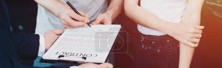 Photo pour Plan panoramique du concessionnaire de voiture tenant presse-papiers tandis que l'homme signature contrat près de la femme - image libre de droit