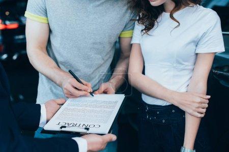 Photo pour Recadrée vue de concessionnaire de voiture tenant le presse-papiers tandis que l'homme signant contrat près de femme - image libre de droit
