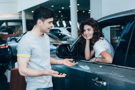 Photo pour Femme gaie assise dans l'automobile près de bel homme debout et gestuelle dans la salle d'exposition de la voiture - image libre de droit