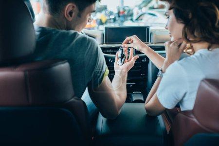 Photo pour Foyer sélectif de la fille donnant des clés à l'homme tout en étant assis dans l'automobile - image libre de droit