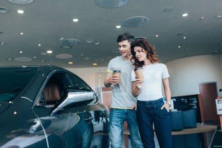 Photo pour Homme gai tenant tasse en papier près de la fille debout avec la main dans la poche tout en regardant l'automobile - image libre de droit