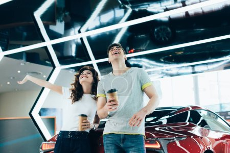 Photo pour Heureux homme et femme rire tout en tenant des tasses en papier près de l'automobile - image libre de droit