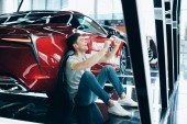 selective focus of happy man sitting on floor near new red car and showing yes gesture