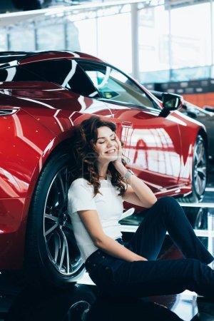 Photo pour Foyer sélectif de femme heureuse avec les yeux fermés assis sur le plancher près de la nouvelle voiture rouge - image libre de droit