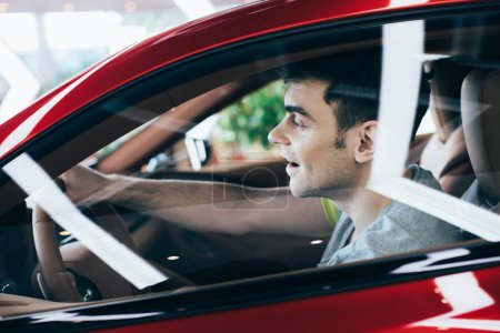 Photo for Selective focus of happy man sitting at steering wheel in new car - Royalty Free Image