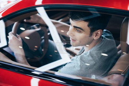 selective focus of smiling man sitting at steering wheel in new car