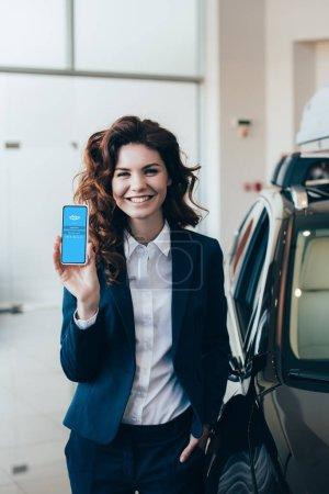 Photo pour Sourire femme d'affaires retenant le smartphone avec l'application de Skype sur l'écran et retenant la main dans la poche - image libre de droit