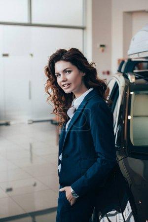 Photo pour Femme d'affaires souriante debout près de la voiture et regardant l'appareil-photo - image libre de droit