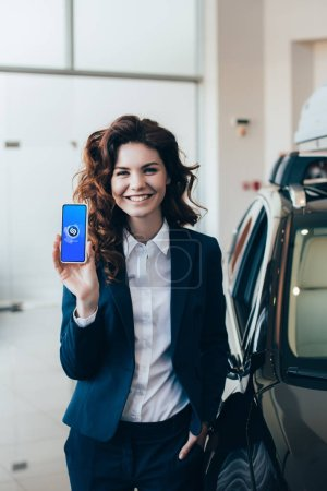 Photo for Smiling businesswoman showing smartphone with shazam app on screen and holding hand in pocket - Royalty Free Image