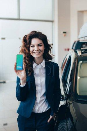 Photo pour Femme d'affaires attirante retenant le smartphone avec l'application de Twitter sur l'écran et retenant la main dans la poche - image libre de droit