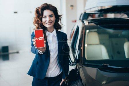 Photo pour Focus sélectif de jolie femme d'affaires tenant smartphone avec application YouTube sur l'écran et tenant la main dans la poche - image libre de droit