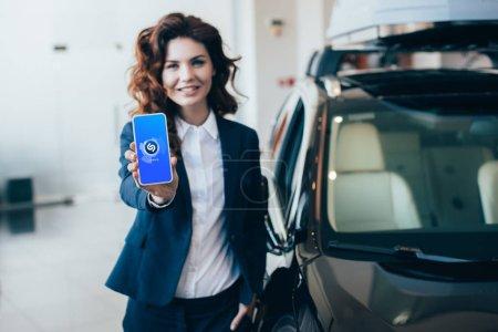 Photo pour Foyer sélectif de la femme d'affaires joyeuse retenant le smartphone avec l'application Shazam sur l'écran - image libre de droit