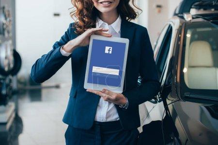 Photo pour Vue partielle de femme d'affaires retenant la tablette numérique avec l'application Facebook sur l'écran - image libre de droit