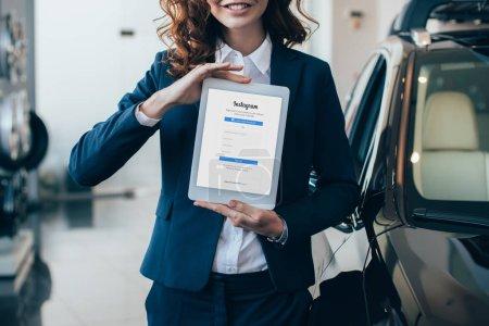 Photo pour Vue partielle de femme d'affaires retenant la tablette numérique avec l'application d'Instagram sur l'écran - image libre de droit