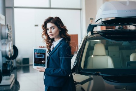 Photo for Serious businesswoman holding digital tablet with booking app on screen and looking at camera - Royalty Free Image