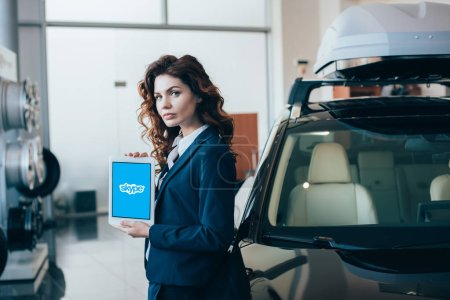 attractive businesswoman holding digital tablet with skype app on screen