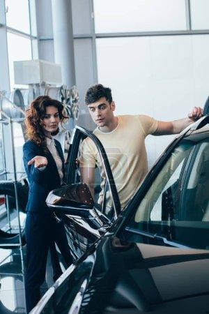 Photo pour Focus sélectif de concessionnaire automobile attrayant et homme bel debout près de nouvelle voiture - image libre de droit
