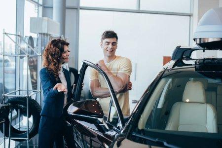Photo pour Focus sélectif de concessionnaire jolie voiture et beau client debout près de nouvelle voiture - image libre de droit