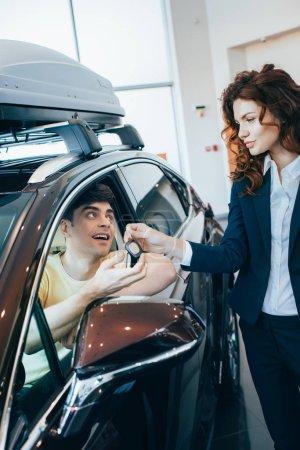 Foto de Enfoque selectivo de hermoso concesionario de coches dando llave del coche a un cliente feliz sentado en un coche nuevo - Imagen libre de derechos