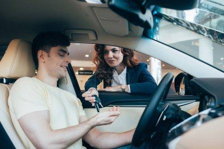 Photo pour Focus sélectif de sourire concessionnaire voiture donnant les clés de l'homme heureux assis dans une nouvelle voiture - image libre de droit