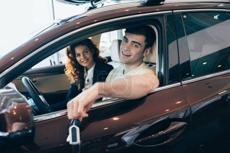 Photo pour Focus sélectif de l'homme heureux tenant les clés de voiture et le concessionnaire de voiture de sourire assis dans la nouvelle voiture et regardant l'appareil-photo - image libre de droit