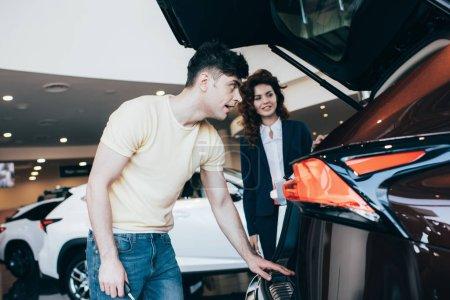 Photo pour Foyer sélectif de bel homme et concessionnaire automobile attrayant debout près de nouvelle voiture - image libre de droit