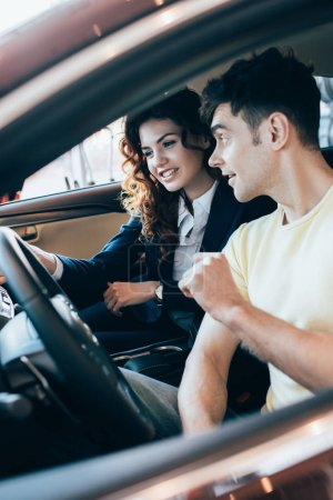 Photo pour Focus sélectif de sourire concessionnaire automobile et bel homme assis dans une nouvelle voiture ensemble - image libre de droit