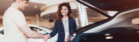 Panoramaaufnahme eines lächelnden Autohändlers und Kunden beim Händeschütteln im Autohaus