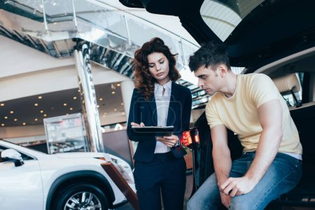 handsome man looking at car dealer writing in clipboard