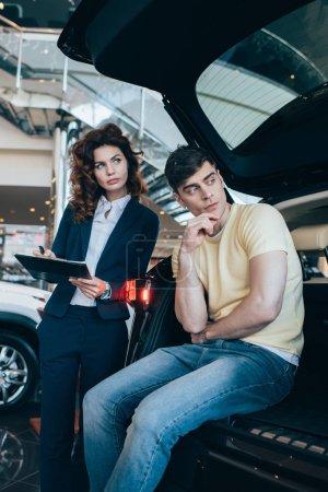 Photo pour Concessionnaire de voiture sérieux et client debout nouvelle voiture dans la salle d'exposition de voiture - image libre de droit