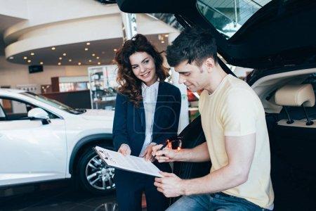 schöner Mann signiert Dokument neben lächelndem Autohändler