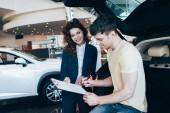handsome man signing document near smiling car dealer